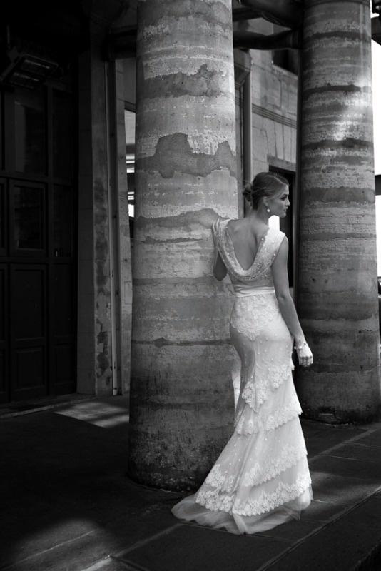 Suknia z delikatnej francuskiej koronki, pod biustem ozdobiona szarfą z kwiatem.