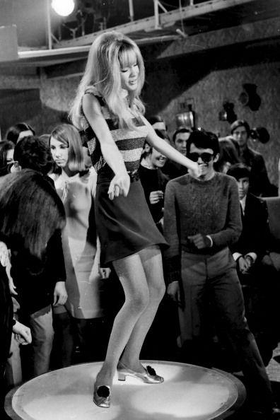 C. 1960s go go dancer mini skirt stripe shirt low heeled shoes long hair bangs vintage fashion style