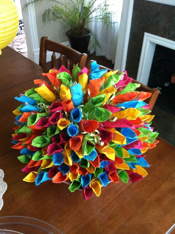 Wrapped clear plasticware in festive colors & arranged them around edge of bowl & built it up.