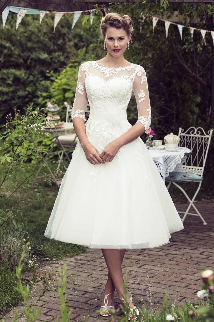 Bonnie - Brighton Belle collection by True Bride brings you this stunning bridal gown for 2016. Designed in-house at the Brighton studio, this collection is dedicated to tea length dresses with a retro edge. Featuring a pretty vintage inspired Guipure Lace, sheer sleeves and a full Fifties style skirt, this dress is ideal for the bride seeking something sassy and chic. A zip up back with button trim and a sheer back finishes the look.