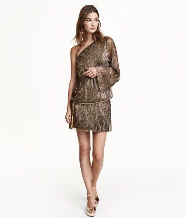 Kurzes, einseitig schulterfreies Kleid aus gecrinkeltem Jersey mit Glitzergarn. Das Kleid hat einen langen weiten Ärmel und einen schmalen Metallgürtel mit Troddeln an den Enden. Jerseyfutter.