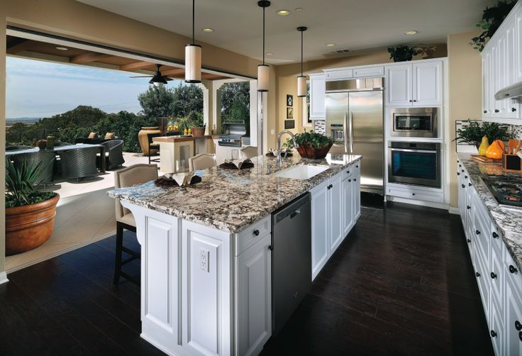 Dreamy white model home kitchen with white cabinets, a granite island, and hidden doors at Hawthorne at Del Sur in San Diego [new homes by Standard Pacific Homes in San Diego].