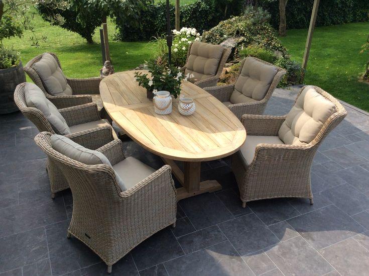 Teakhouten tafel in een ovalen vorm met luxe stoelen van vlechtwerk