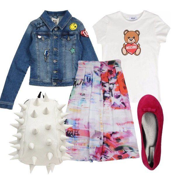 Outfit composto da gonna in tela a fantasia multicolore, t-shirt in jersey con stampa, giubbotto di jeans con applicazioni, ballerine in pelle effetto scamosciato e zaino bianco in ecopelle.