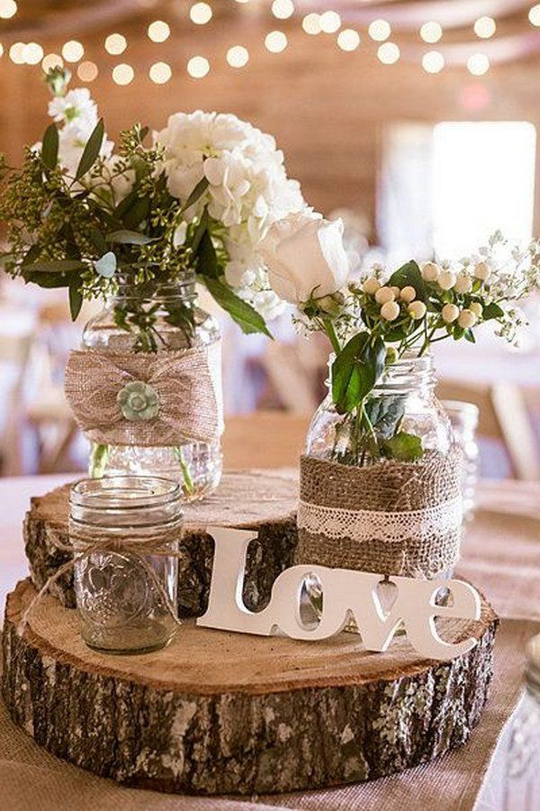 Burlap Wrapped Mason Jars Stacked atop Tree Trunk Slices