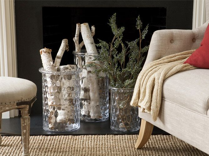 When a crackling fire isn't occupying your fireplace (or if you have a non-functioning fireplace), it can still be a stunning focal point. Brighten your dark and empty firebox with a stylish display. Fill large hurricane vases with natural elements, such as birch logs or greenery.