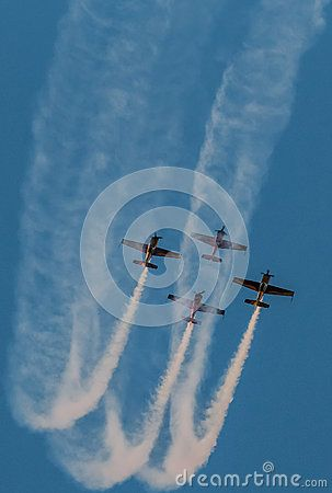 A team of four airplanes in yellow flying together high up in the sky on an air show.  Airplanes on air show with smoke trails. Airplane performing difficult maneuver in the sky. Blue clear sky. Blue background.
