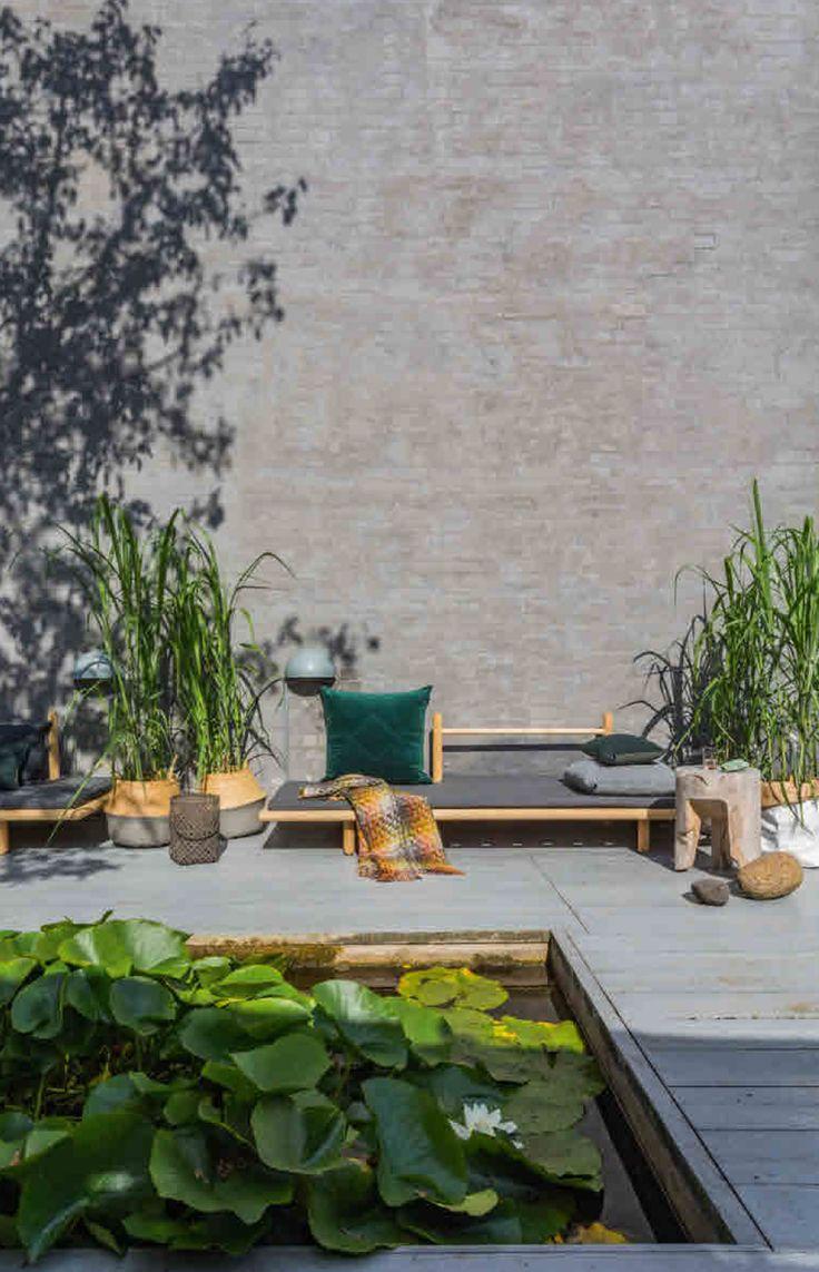 Buitenruimtes - door Glotti Press. De waterpartij met waterlelies is altijd een droom geweest van Beinta Unni Marr. De planten hebben weinig verzorging nodig en vormen een idylle midden op het terras. Het daybed Beddo is van Skagerak. De wandlampen van gegalvaniseerd staal komen van een doe-het-zelfzaak. Het kleed is van Missoni en de kussens zijn van Hay en Louise Roe. Mand met hengsel van Bloomingville, lantaarns van Broste Copenhagen