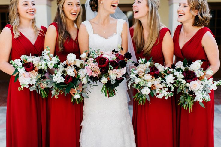the bride and her bridesmaids enjoying a fun moment before the wedding. the bridesmaids wore dresses of deep red and carried beautiful lush and full bouquets of red charm peony, white ranunculus, white stock, quicksand rose, Kiera garden rose, chocolate cosmos, white majolica spray rose, scabiosa pods, peach celosia, pink celosia, seeded eucalyptus, dusty miller