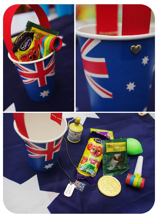 Australia Day loot. Great party favour idea for the kids. Bucket made with paper party cups, strips of red card and brads (paper fasteners). Filled with Aussie themed loot - Caramello Koala, Aussie coin, Beechworth honey, Australian sultanas, Aussie flag dog tag necklace, party blower.