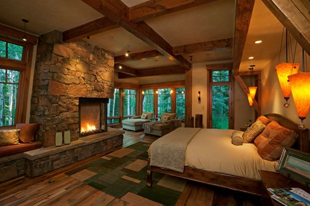 Rustic Contemporary - In this master bedroom, the contemporary fireplace design pairs well with the moss rock. Reclaimed white oak floors add a layer of rusticity to the space, and once again, there is a wonderful feeling of bringing the outdoors into the room with the mix of glass, stone and reclaimed wood.