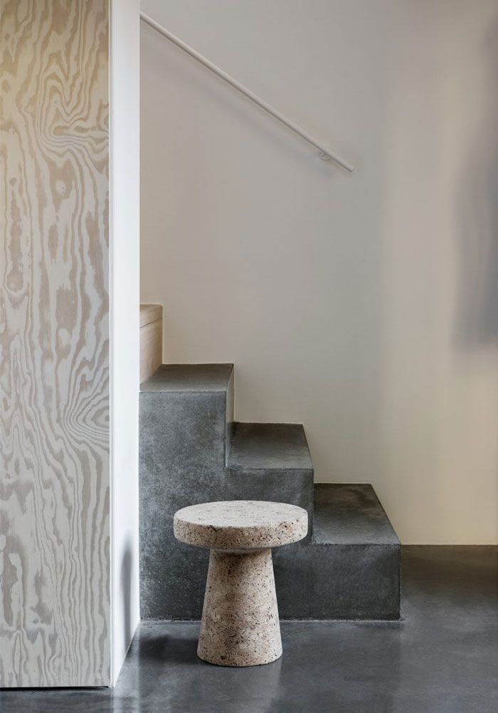 Den varma grå nyansen på betongen i kombination med plywooden gör att det…