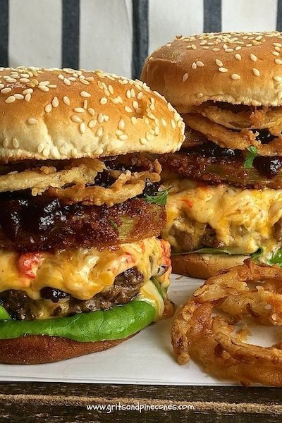 The Ultimate Southern Style Burger offers a unique twist to a classic hamburger and features melted pimento cheese fried green tomatoes, onion rings, and tomato jam. via @gritspinecones