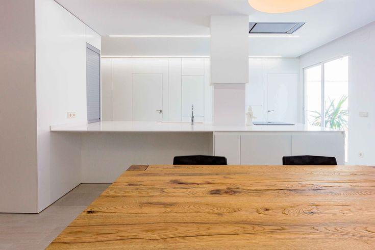 Cocina comedor minimalista con mesa de madera rústica en reforma de casa. Chiralt Arquitectos Valencia.