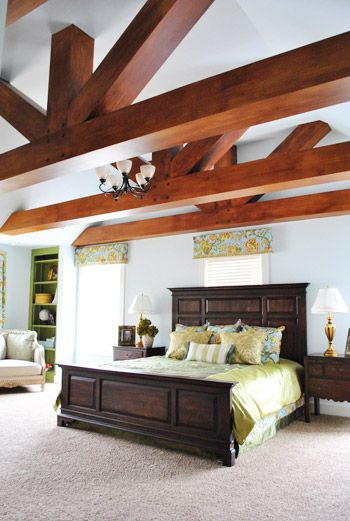 "the designer of the ""Vintage Rediscovered"" home had this outside-the-box solution for the monstrous ceiling in the master bedroom – she had the builder add faux beams (surprise, they're actually just painted drywall)."