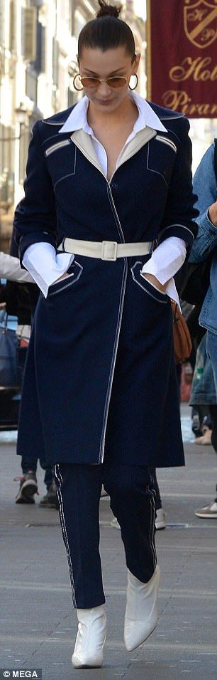 Wrapped up: The Californian beauty's navy ensemble featured a knee-length trench coat that highlighted her svelte figure with a cream waist-belt which complemented the garment's cream detailing
