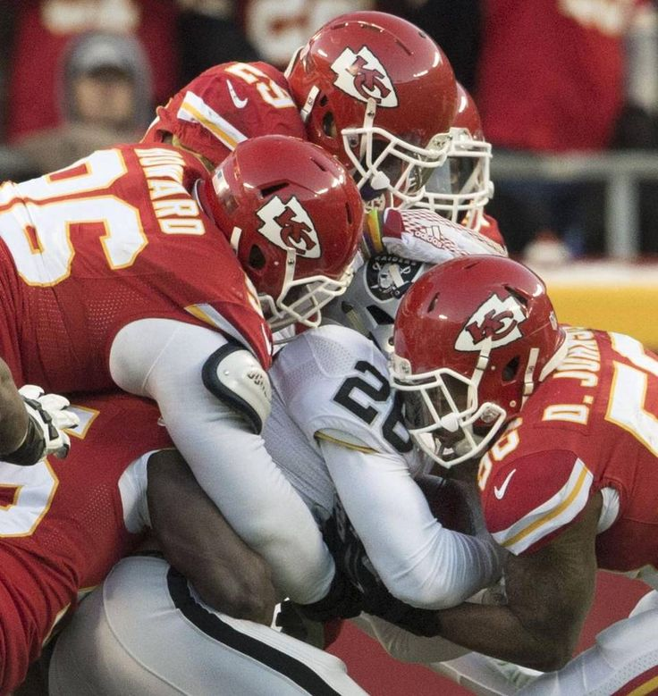 The Chief's defense gang tackled Oakland Raiders running back Roy Helu (26) as Kansas City Chiefs inside linebacker Derrick Johnson (56) tired to strip the ball in the second quarter during the Kansas City Chiefs and Oakland Raiders football game at Arrowhead Stadium on January 3, 2016 in Kansas City, Missouri.