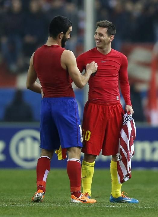 Barcelona's Lionel Messi from Argentina exchanges his shirt with Atletico's Arda Turan during a Spanish La Liga soccer match between...