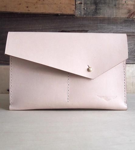 Shaped like an angled envelope, the clutch purse closes with a metal stud. The leather will soften and get darker with use, only looking better with age.