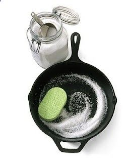 To clean a cast iron skillet, toss about 1/2 cup coarse salt into the pan and rub with a soft sponge. The salt removes excess oils and takes off the bits of food without messing with the seasoning of the pan.