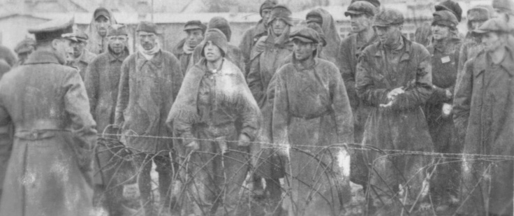 """Stalag XVIIIA, Wolfsberg, Austria: A group of Soviet POWs confer with a German army officer across the barbed wire. Under the circumstances, the conversation seems to be """"amiable."""" The photo was taken by a British POW; the presence of British captives meant that this Stalag was borderline better than other camps since the Germans treated western soldiers much better than the Russians."""