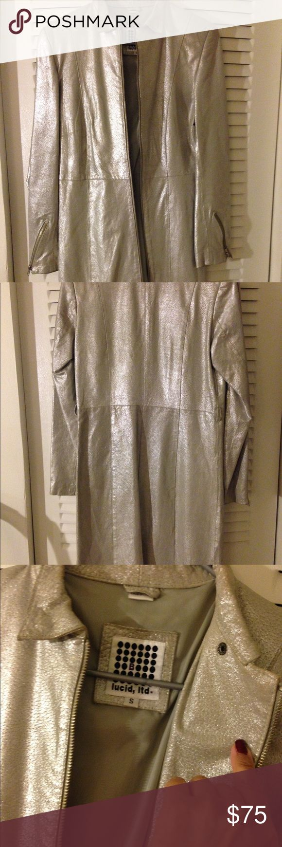 """Lucid  Metallic Silver Genuine Leather Coat Small Women's Lucid metallic silver soft 100% genuine leather trench -style  jacket coat. Size small or 4 - 6. Slight angle zippered front and sleeves. Great condition besides the missing thin 0.25"""" belt which I didn't use anyway. Must have tossed when replacing garment bags. Jackets & Coats Trench Coats"""