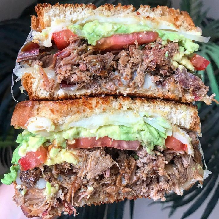 Smoked beef brisket bacon grilled hamburger and pulled pork topped with pepper jack and Swiss cheese beefsteak tomato avocado and sweet onion all on toasted white bread. [1080  1080]