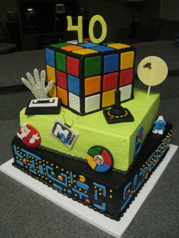 80s Themed Surprise 40th Birthday Cake: Rubik's Cube, Michael Jackson's Studded Thriller Glove, Cassette Tape, Ghostbusters, MTV, Atari Joystick, Simon Game, I LOVE 80s, ET & Elliott's Bike Flight, Smurf & Pacman Game Board