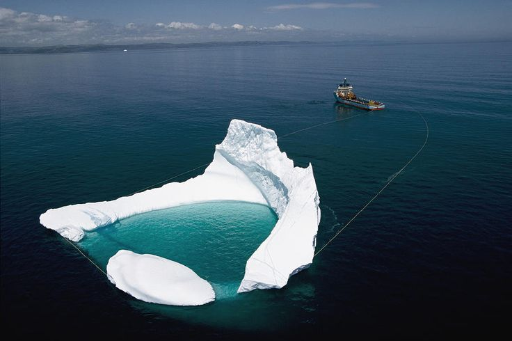 Incredible Picture of a Ship Towing an Iceberg Off The Shore of Newfoundland