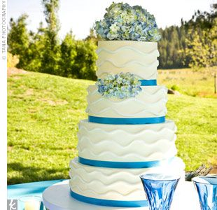 Walt and Devin's three-tiered, buttercream wedding cake was decorated with waves and blue ribbons to match the lakeside theme. It featured two flavors: Tahitian vanilla cake with huckleberry filling, and lemon poppy-seed cake with huckleberry and lemon buttercream filling.