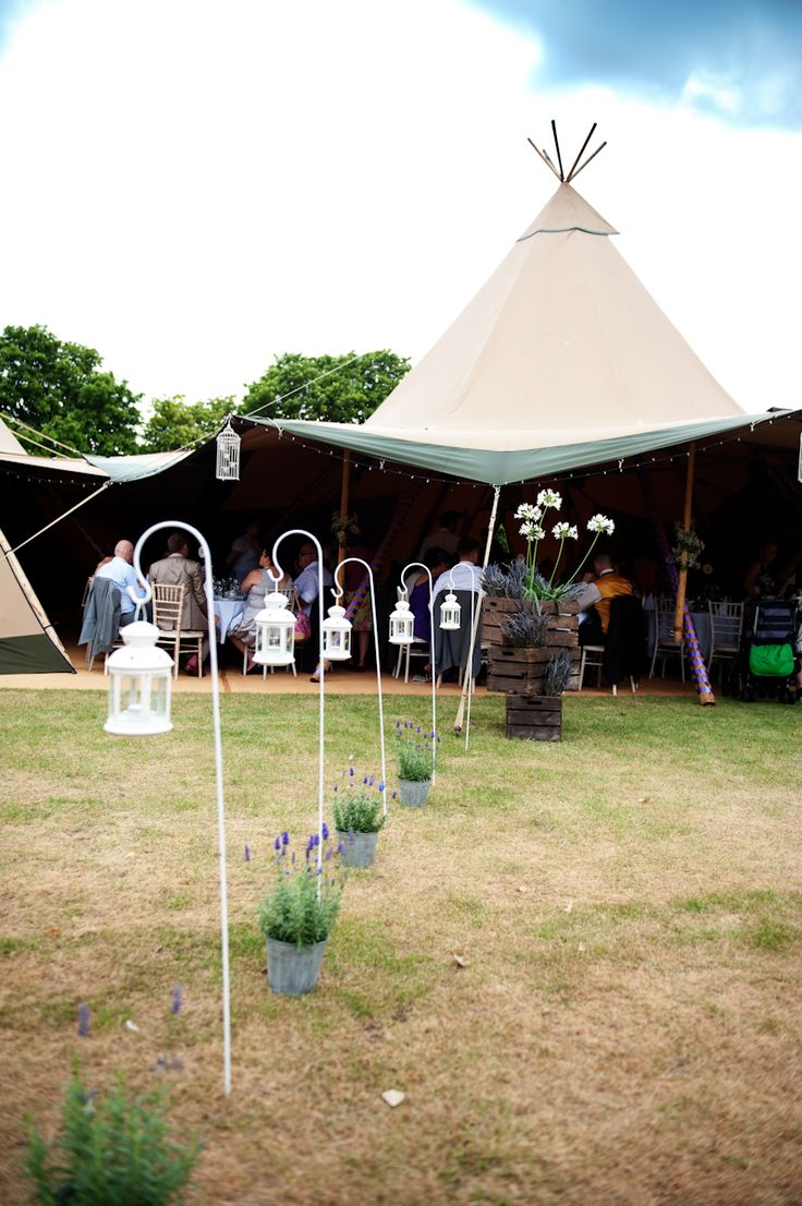 A great idea to lay out your walkway to your tipi wedding reception. White Shepard hooks and lanterns for the evening to light the way and rustic style potted plants for added colour
