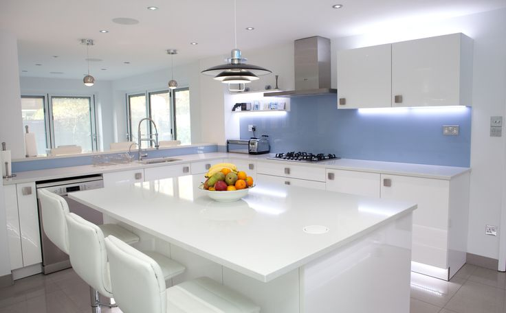 White Gloss Nolte Kitchen with bright blue glass splashbacks and ambient lighting