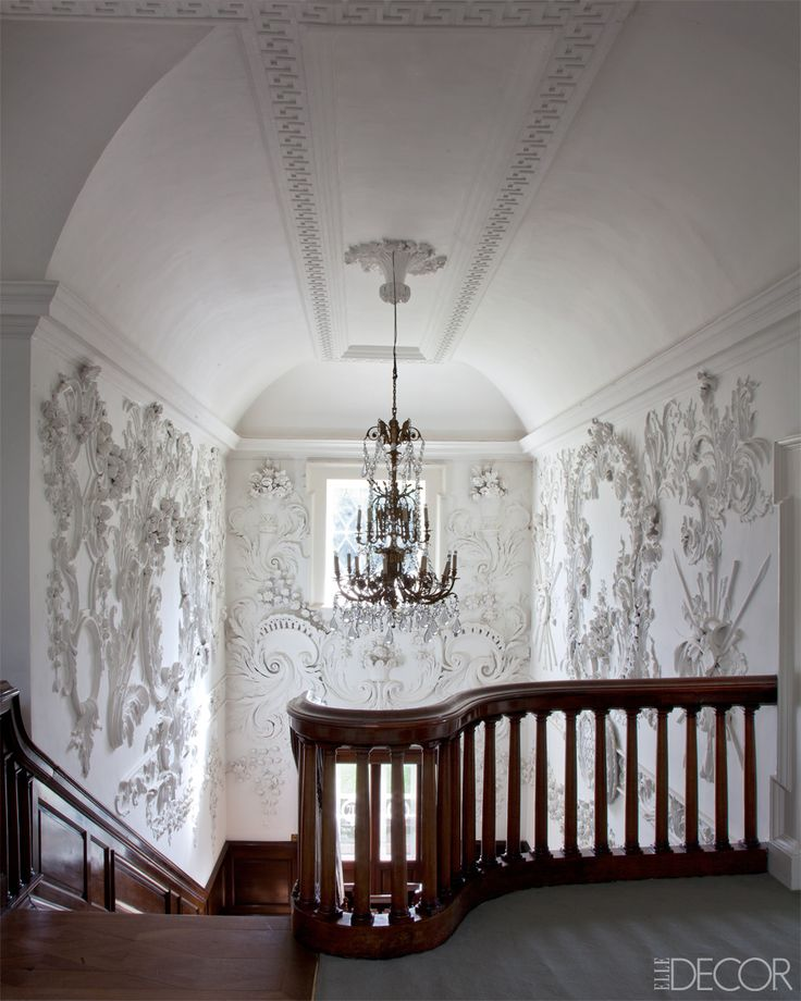 Russborough House Ireland - Irish Country Estate Design, @ELLE DECOR photo by James Fannell, Baroque stucco, thought to be the work of Irish apprentices, lines the walls surrounding the 18th-century mahogany staircase; the chandelier is Georgian.