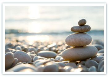 Photo of stacked rocks by water