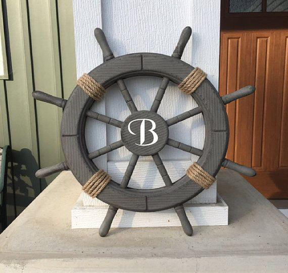 ** PLEASE TYPE THE LETTER YOU WOULD LIKE IN THE CENTER OF THE WHEEL IN THE MESSAGE TO SELLER. USE THE DROP DOWN MENU TO SELECT THE COLOR OF THE LETTER **  This Antique Grey Ship Wheel is 18 and combines a bold finish with quality craftsmanship to make this the perfect nautical wall hanging to accent your home. Ideal for those who love rustic and vintage nautical wall art, this beach decor will leave your guests in awe. A perfect custom wedding gift. Steering wheel has eight spokes…