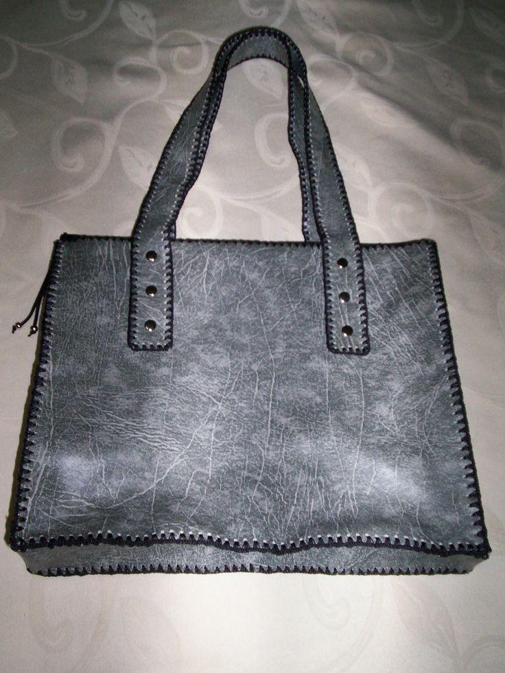 Bolso - cartera, ecocuero gris jaspeado, con fuelle y cierre superior.