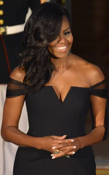 Michelle Obama wore a black off-the-shoulder Vera Wang Collection mermaid gown to the China state dinner, 9/25/15. The custom dress was silk crepe with a V-neckline. Fitted, with sheer sleeves, it skimmed the floor with its tulle flounce. The first lady's hair was gathered in a vintage sultry side sweep.