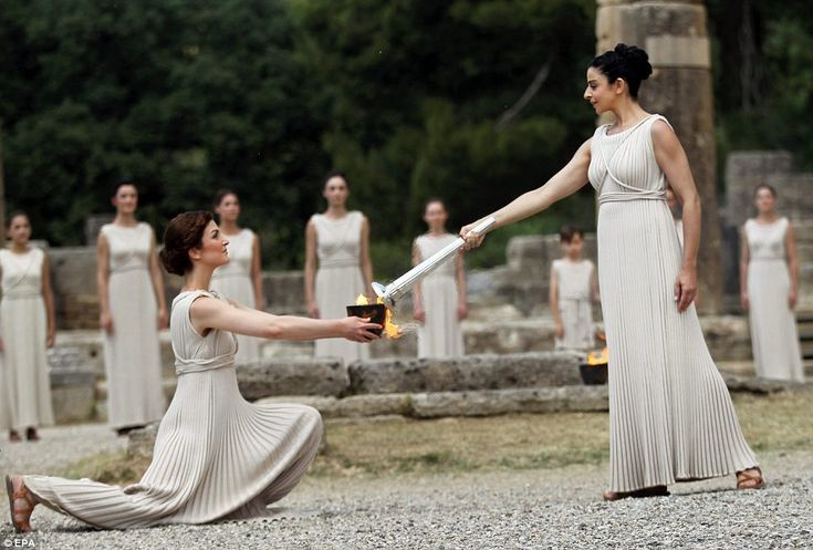 And so it begins: Actress Ino Menegaki (right), in the role of the High Priestess, lights the torch of the Olympic Flame during the Lighting...
