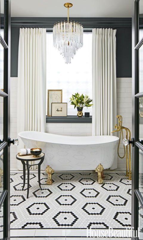 "An Alexander McQueen skull pillow was the catalyst for this daring en suite bathroom in Chicago's trendy Wicker Park neighborhood. ""I wanted drama!"" says designer SuzAnn Kletzien, who notes that placing a modern, jewelry-inspired chandelier over a claw-foot tub ""definitely satisfied that need."""