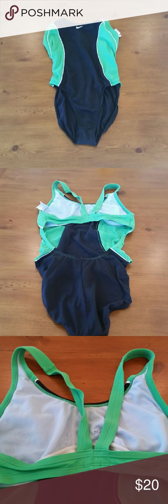 Nike Racing Swimsuit Green and black Nike racing swimsuit. In good condition. Worn to practice a few times before the team suits came in. Small holes made inside to take those obnoxious booby cups out... as seen in 3rd photo. Nike Swim One Pieces