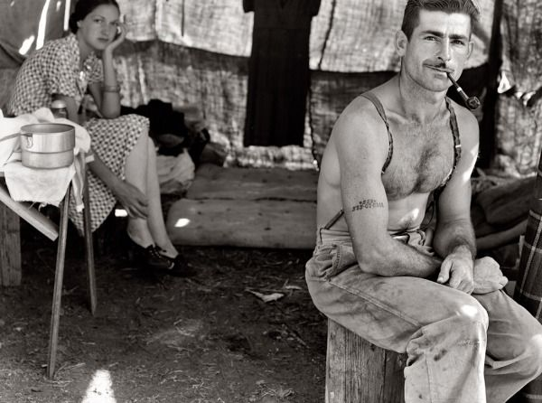 "Oregon, August 1939. ""Unemployed lumber worker goes with his wife to the bean harvest. Note Social Security number tattooed on arm."""