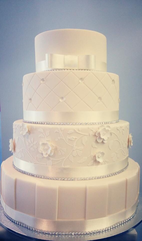 Four tiered fondant detailing wedding cake in white. Traditional and classic beauty