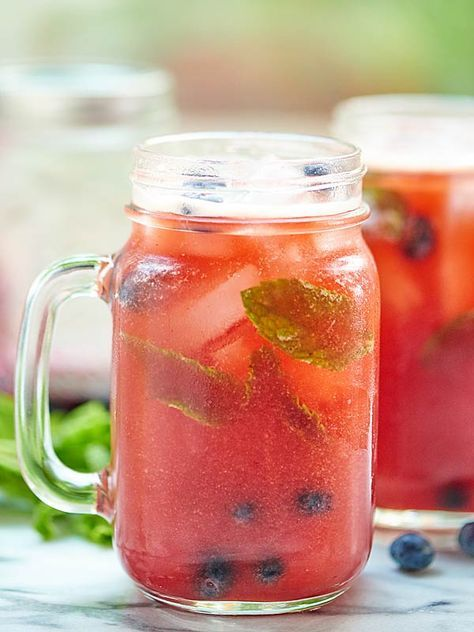 Blueberry Peach Mojito - The drink of all summer drinks! Peach puree, a homemade blueberry simple syrup, fresh mint, and rum.