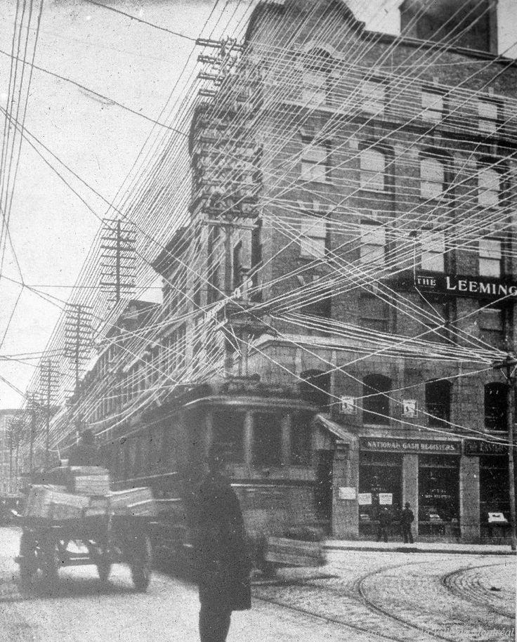 Photographie de la rue Notre-Dame vers l'ouest, à l'intersection de la rue Saint-Laurent. Un tramway, une charrette et un piéton traversent l'intersection. Des rails de tramway sont visibles sur le pavage de la rue. Des câbles de tramway, des fils et...