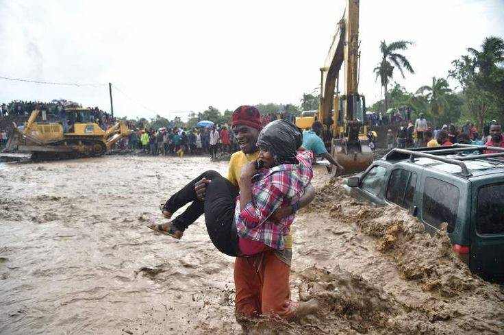 A woman is carried across the river La Digue in Petit Goave where the bridge collapsed during the rains of the Hurricane Matthew, southwest of Port-au-Prince, October 5, 2016. Haiti and the eastern tip of Cuba -- blasted by Matthew on October 4, 2016 -- began the messy and probably grim task of assessing the storm's toll. Matthew hit them as a Category Four hurricane but has since been downgraded to three, on a scale of five, by the US National Hurricane Center. Hector Retamal, AFP/Getty…
