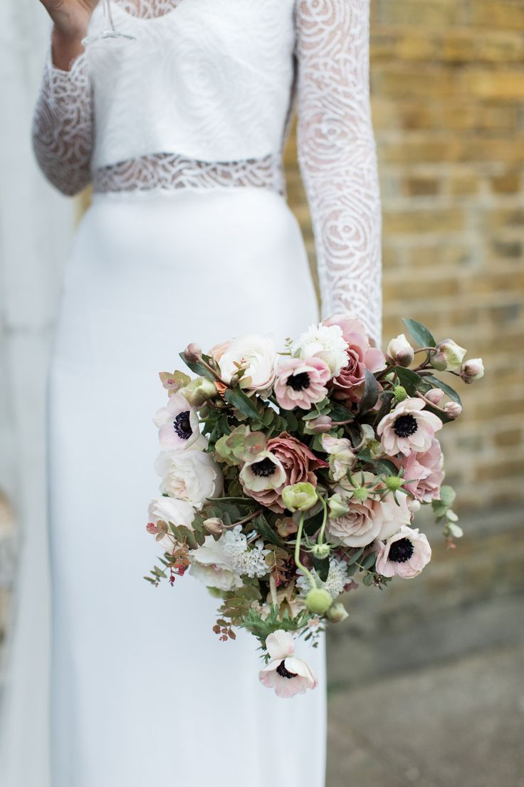 Pale pink, dusty rose, and ivory bouquet with anemones, roses, ranunculus, scabiosa, hellebores, and baby eucalyptus.