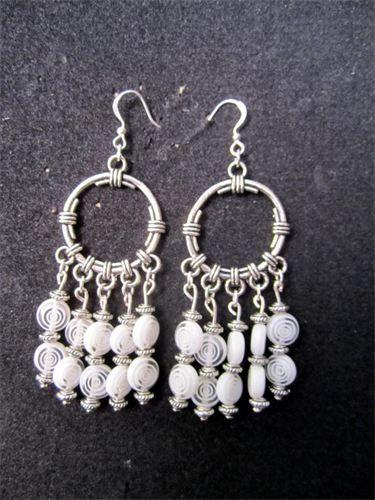 Spiral - 9    Långa örhängen med cirkelformade fästen och detaljer i silverpläterad metall. Hängande glaspärlor i Vit/Transparent Spiralmönster samt nickelfria krokar. Frakten är inkluderad i priset.    Pris:  190 kr