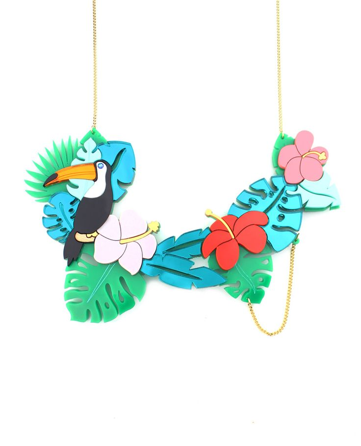 Toucan necklace, The toucan, with its enormous and majestic orange beak sits on a tree branch amongst all the plants in the leafy jungle. You will be surprised by its beautiful black and white plumage, although you won't be able to look away from its gorgeous beak.  Laser-cut opaque and mirror toucan with a blue swarovski element with leaves in mirror and opaque acrylic with colourful flowers. Made and assembled by hand.  LIMITED EDITION to 15 pieces.