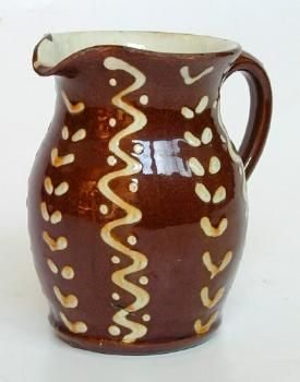 This earthenware jug was made in 1947 by A. Schofield at the Wetheriggs Pottery in Clifton Dykes, Cumbria. Slipware, which uses slip (semi-liquid clay and water) on a contrasting-coloured clay body, often for decoration, is a traditional form of pottery in Great Britain. The inside of this jug has a cream-coloured glaze, and the outside is decorated with a trailed slip design in cream and covered in a clear glaze. (60/626)