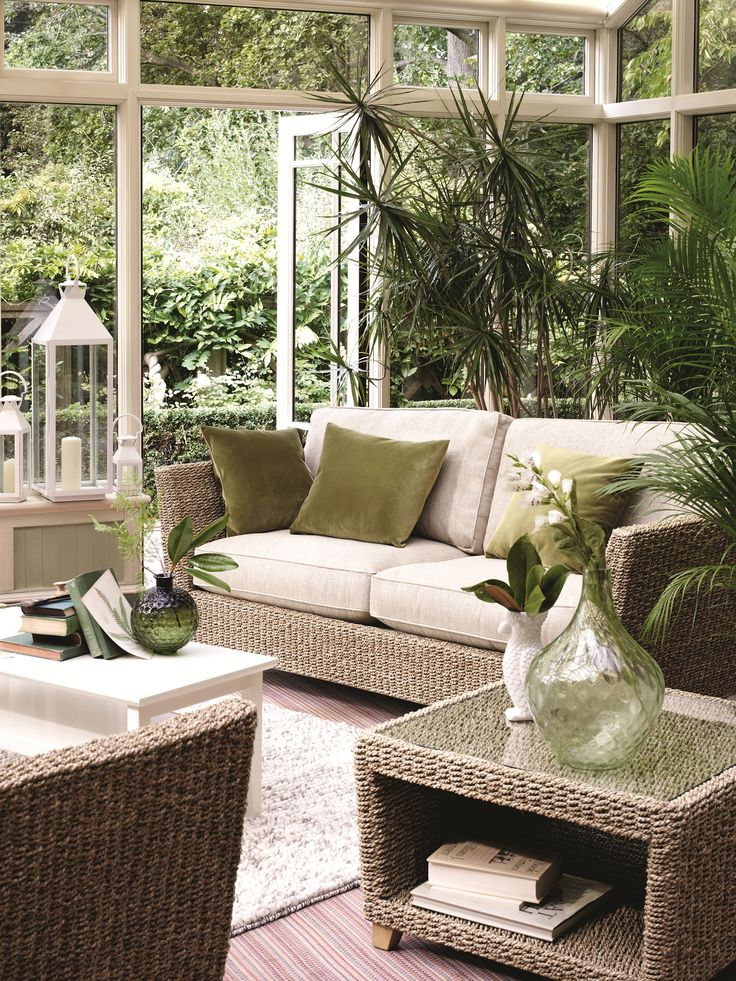 sun and garden rooms neutral palette wicker furniture window wall greenery